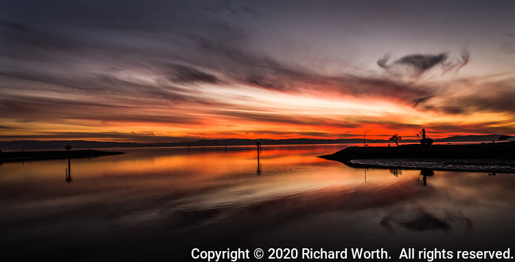 San Francisco Bay sunset panoramic composed from multiple images captured on a winter afternoon at the San Leandro Marina.