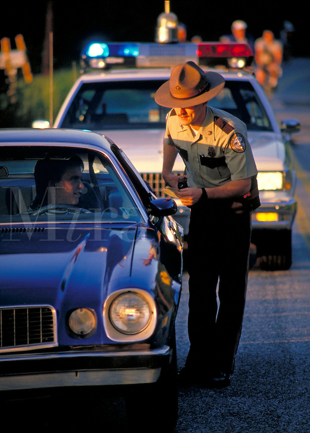 A policeman looks at license of male driver at traffic violation stop along street. state police and teenager.