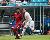 CHARLOTTE, NC - JUNE 23: Lucas Cavallini #19 and Jorge Kindelan #19 vie for the ball during a game between Cuba and Canada at Bank of America Stadium on June 23, 2019 in Charlotte, North Carolina.