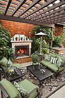 Outdoor garden room with shade pergola and fireplace in small space urban townhome patio garden