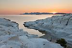 Greece, South Aegean, Cyclades, Milos island, Sarakiniko: Beach and volcanic rock formations at Sarakiniko on north coast with sun rising over Kimolos island in distance | Griechenland, Suedliche Aegaeis, Kykladen, Insel Milos, Sarakiniko: Strand und Vulkangesteinformationen an der Nordkueste, Sonnenaufgang am Horizont ueber Kimolos island