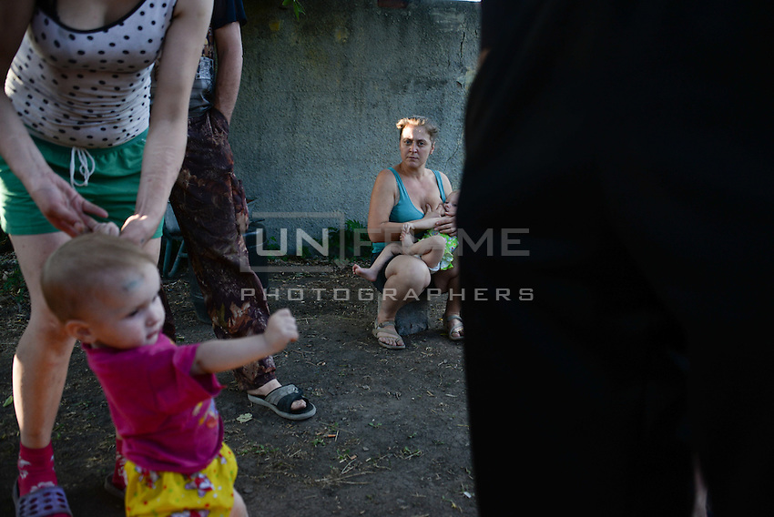 Mother breastfeeding her child in front of a bomb shelter in between shellings. Donetsk, Eastern Ukraine.