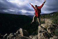 Hiker jumps between rocks on a mountain
