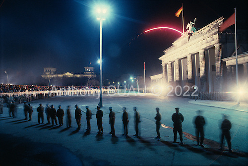 East Berlin, East Germany<br /> November 10, 1989 <br /> <br /> West Germans sit on the wall to look at the guards at the east border near Brandenburg Gate, Germans gathered at the wall after the East German government lifted travel and emigration restrictions to the West the day before.