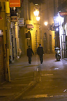 A night street with two men walking. Montpellier. Languedoc. France. Europe.