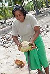 A local i-Kiribati woman removing the husk from a coconut in a remote village of Poland on the island of Kiritimati in Kiribati