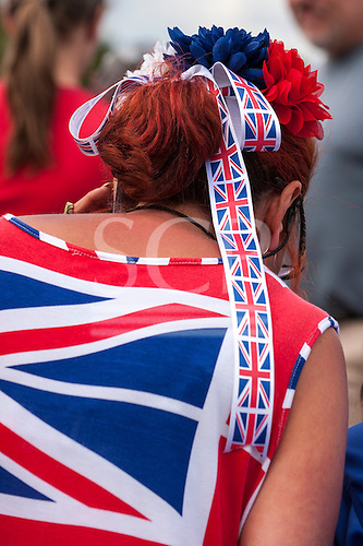 England. Woman with Union Jack flag bow in her hair and T shirt.