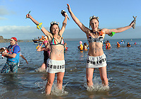 Pictured: Two young women jump in the freezing cold sea in Tenby, west Wales, UK. Monday 26 December 2016<br /> Re: Hundreds of people in fancy dress, take part in this year's music-themed charity event, the Boxing Day Swim in Tenby, Pembrokeshire, Wales, UK