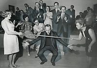 Doing A Thank You Limbo last night; Father Michael O'Connor weaves his way beneath a stick held by Mrs. Pamela Cruickshank to demontrate Trinidad limbo dance to guests at a party in his honor at Maple Community Centre. Mrs. Cruickshank founded a group that sends supplies to children at his Trinidad school.<br /> <br /> Photo : Boris Spremo - Toronto Star archives - AQP