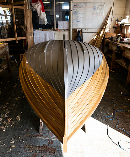 The sweet harmony of a classic clinker-built boat as she is coated  her paint and varnish