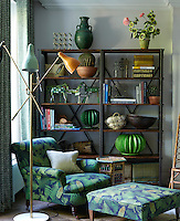 A retro floor lamp complements the choice of fabric used to upholster the armchair and matching footstool in the living area