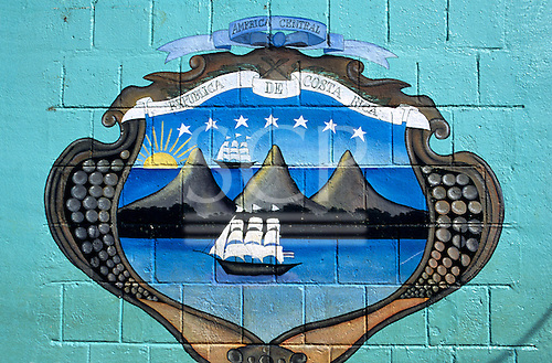 Costa Rica. National coat of arms; three volcanoes against the ocean with sailing ships and seven stars, rising sun, paited on a wall.