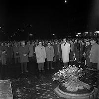 19 janvier 1962. Scène de manifestation : au 1er plan quatre hommes se recueillent devant une gerbe de fleurs (vue de face) ; en arrière-plan foule. Vue de nuit. Cliché pris lors d'une manifestation anti OAS (Organisation de l'Armée Secrète) organisée par le font syndical commun à la suite d'une série d'attentats perpétrés à Toulouse dans la nuit du 15 au 16 janvier 1962.