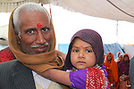 A man holds his granddaughter in one of the pilgrim tents at the Maha Kumbh Mela.