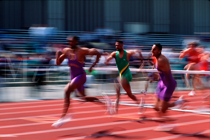 Hurdlers sprinting after clearing a hurdle.