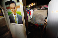 """Thailand. Bangkok. A young man, who lives as a squatter  in Tha Tian, with his clothes hanged . The man works as a coolie in Tha Tian. A picture of King Bhumibol is taped on the wall. Bhumibol Adulyadej (born 5 December 1927), is the current King and Head of the State of Thailand. Publicly acclaimed """"the Great"""" he is also known as Rama IX. Having reigned since 9 June 1946, he is the world's longest-serving current head of state and the longest-serving monarch in Thai history. Tha Tian is a community located in the downtown area and in the center of the urban historic district, called Koh Rattanakosin. 28.03.09 © 2009 Didier Ruef"""