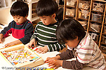 Preschool Headstart 3-5 year olds group of boys playing with puzzle showing word and object horizontal