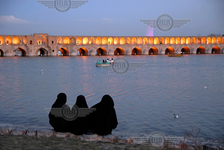 Three women wearing black chadors sit beside the Zayandeh River and watch the sunset over the Allahverdi Khan Bridge (Si-o-se-pol).