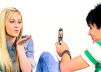 Teenage boy taking a picture of his girlfriend on his cellphone camera.