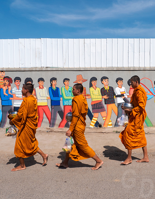 Buddhist Monks collecting their Alms in the rural town of Battambang, Cambodia Wall murals along the roads as Monks walking by