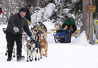 Thursday March, 2012   An Ophir volunteer helps Colleen Robertia leave the checkpoint.   Iditarod 2012.
