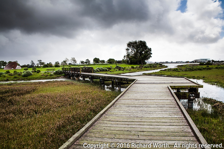 Clouds fill the sky over an observation platform that stretches from a path along the shore line into San Leandro Bay at the Martin Luther King Jr. Regional Shoreline in Oakland, California.