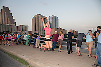 Fit attractive Austin woman leaps for joy at a bat watching party on the Congress Ave. Bat Bridge in Austin, Texas.