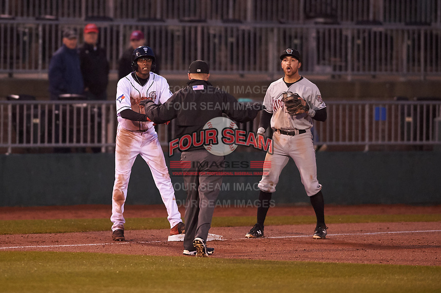 Wisconsin Timber Rattlers Connor McVey (6) reacts to umpire Lance Seilhamer's call as Reggie Pruitt (5) is ruled safe at third base during a Midwest League game against the Lansing Lugnuts at Cooley Law School Stadium on May 2, 2019 in Lansing, Michigan. Lansing defeated Wisconsin 10-4. (Zachary Lucy/Four Seam Images)