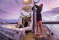 A tourist poses on the dock with her catch, an ono (or wahoo), next to the sport fishing boat Boom Boom, Ka'ena Point, O'ahu.