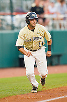 Pat Blair #11 of the Wake Forest Demon Deacons takes his lead off of third base against the Miami Hurricanes at NewBridge Bank Park on May 25, 2012 in Winston-Salem, North Carolina.  The Hurricanes defeated the Demon Deacons 6-3.  (Brian Westerholt/Four Seam Images)