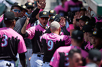 Jake Burger (9) of the Charlotte Knights is greeted by teammates after hitting a 2-run home run against the Gwinnett Stripers at Truist Field on May 9, 2021 in Charlotte, North Carolina. (Brian Westerholt/Four Seam Images)