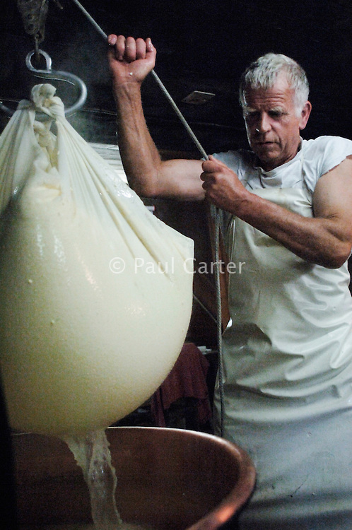 Scooping up the curd from the cauldron and lifting it with the ceiling trackway pully system...Cowherd and cheesemaker spends 100 days in the summer, high up in the mountains, tending cows and pigs and making cheese at Balisalp and Käserstatt near Meiringen, Switzerland.