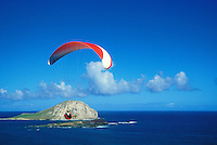 A man enjoys paragliding near Rabbit island (Manana Isl.) and Makapuu pt. on Oahu's eastern coastline.