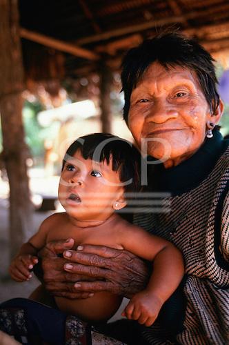 Koatinemo village, Brazil. Smiling elderly Assurini Indian woman holding her young granddaughter.