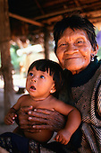Koatinemo village, Brazil. Smiling elderly Assurini Indian woman holding her young granddaughter.