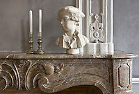 A pair of mercury candlesticks and the bust of a young man are displayed on the original marble mantelpiece in the salon