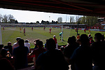 Home supporters in the shed watching the early action as Ilkeston Town (in red) host Walsall Wood in a Midland Football League premier division match at the New Manor Ground, Ilkeston. The home team were formed in 2017 taking the place of Ilkeston FC which had been wound up earlier that year. Watched by a crowd of 1587, their highest of the season, the match was top versus second, however, the visitors won 4-0 and replaced their hosts at the top of the division on goal difference with two matches to play