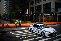 """NEW YORK, NY - AUGUST 4: NYPD officers stand guard next to water barriers used to prevent flooding at the South Street Seaport as city gets ready for tropical storm Isaias on August 4, 2020 in New York City. The Tri-State area """"New York, New Jersey and Connecticut"""" is preparing for torrential rain, strong winds from Tropical storm Isaias. (Photo by Eduardo MunozAlvarez/VIEWpress)"""