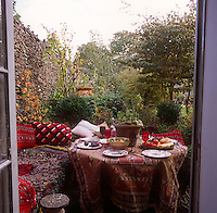 A secluded seating area in a garden with a round table in the shelter of a stone wall. The table has a patterned cloth and red cushions are placed on the seat.