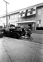 Humanitarian G.I.'s.  Firefight where G.I. pushes little kid under jeep for protection, Santo Domingo, May 5, 1965.  Jack Lartz.  (USIA)<br /> NARA FILE #:  306-DR-2-8<br /> WAR & CONFLICT BOOK #:  378