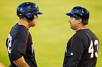 Kannapolis Intimidators manager Julio Vinas #43 talks to runner Kevan Smith #32 at third base during the game against the Hickory Crawdads at CMC-Northeast Stadium on April 7, 2012 in Kannapolis, North Carolina.  (Brian Westerholt/Four Seam Images)