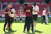 Brentford Manager, Thomas Frank hugs one of his coaching team as they celebrate winning the Championship Trophy and promotion to the Premier League during Brentford vs Swansea City, Sky Bet EFL Championship Play-Off Final Football at Wembley Stadium on 29th May 2021