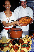 Sao Paulo, Brazil. Chef & smiling waitress holding a dish of bolinhos de baccalhau at a buffet. Hilton Hotel.