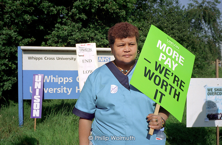 Domestic Peri Alta on the picket line at Whipps Cross Hospital.  She has worked at the hospital for two and a half years and takes home £280 per fortnight.  The campaign  for a living wage by contract catering, portering and cleaning staff employed by multinational ISS Mediclean is backed by Unison and The East London Citizens Organisation (TELCO); Walthamstow, 2003.