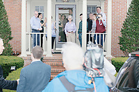 People watch as Democratic presidential candidate and South Bend mayor Pete Buttigieg arrives to speak at a house party with the Bedford Democrats in Bedford, New Hampshire, on Sat., Apr. 20, 2019. The candidate stood on a chair throughout his speech.