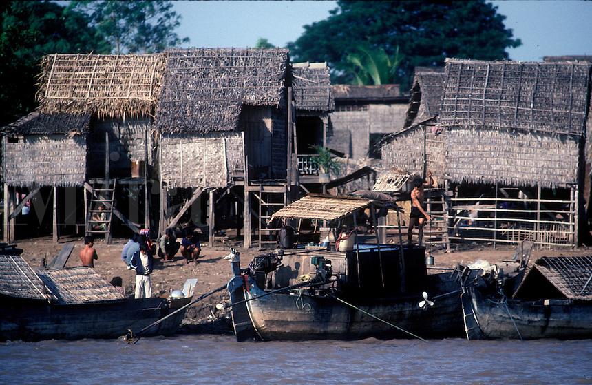 Boats dock along shore line of Vietnamese village in the southern Delta region.