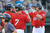 Left fielder Trenton Kemp (17) of the Greenville Drive is congratulated after hitting a home run in a game against the Greensboro Grasshoppers on Thursday, July 14, 2016, at Fluor Field at the West End in Greenville, South Carolina. Sao shown are Austin Rei, left, and J.T. Watkins (7). Greenville won, 3-1. (Tom Priddy/Four Seam Images)