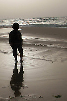 "Palestinian boy play on the beach  at  sunset time, in southern Gaza Strip March,12,2007.""photo by Fady Adwan"""