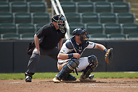 Queens Royals catcher Ryan Dudney (15) sets a target as home plate umpire Grant Akins looks on during the game against the Mars Hill Lions at Intimidators Stadium on March 30, 2019 in Kannapolis, North Carolina. The Royals defeated the Bulldogs 11-6 in game one of a double-header. (Brian Westerholt/Four Seam Images)