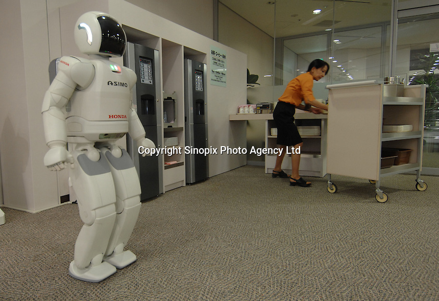 """The Asimo robot built by Honda in it's first test environment, the Honda headquarters in Tokyo where it lives in the office and performs simple tasks. Asimo is one of the most advanced humanoids in the world and is being developed as a """"home"""" help robot."""